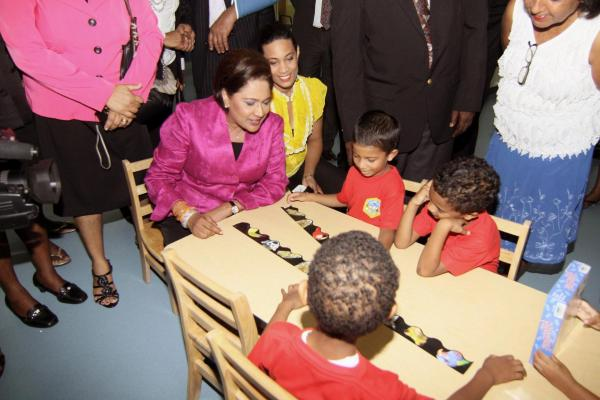 Caption: Prime Minister, Kamla Persad-Bissessar and Chairman of the Tunapuna-Piarco Regional Corporation engage in childplay with these children from the the Bon Air ECCEC.