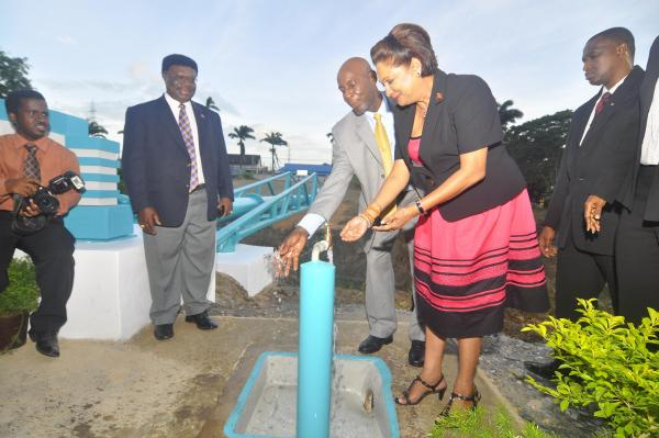 Caption: The Prime Minister and Minister of Public Utilities Emmanuel George turn on the pipe.