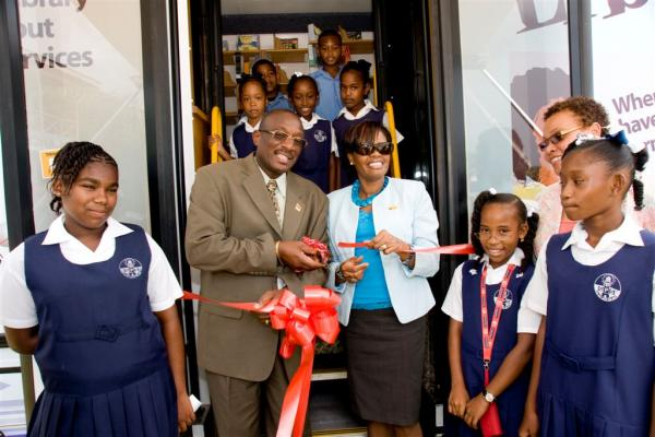 Caption: Minister Winston Peters and Annette Wallace cut the ribbon to open the mobile library.