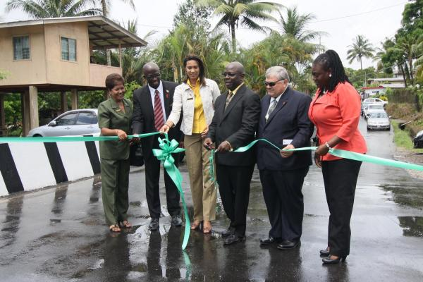 Caption: Dr. Lincoln Douglas, Minister in the Ministry of the People and Social Development and cuts the ribbon for the new bridge at the Arima Old Road, D'Abadie. He is assisted by Khadijah Ameen, Chairman of Tunapuna/Piarco Regional Corporation, Mayor of Arima Ghassan Youseph and Erwin Hope, Councillor for La Florissante/Clever.